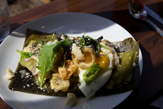 Spring Onion Tamale  Sunnyside egg, refried pinto beans, lime chicharonnes, Queso fresco, serrano chili aioli, pickled califlower