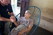 Derrick praying with 80 year old Julia who is in poor health.