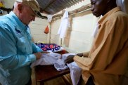 Charles inspecting some of the latest uniforms made by the tailoring school